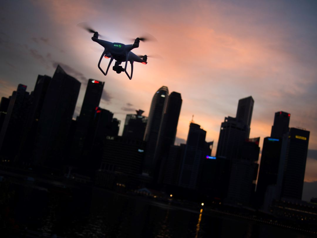 Drones company over city in a sunset